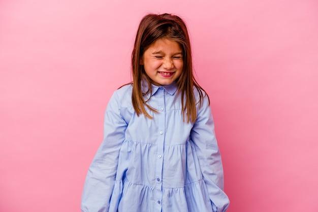 Маленькая девочка, изолированная на розовой стене, смеется и закрывает глаза, чувствует себя расслабленной и счастливой