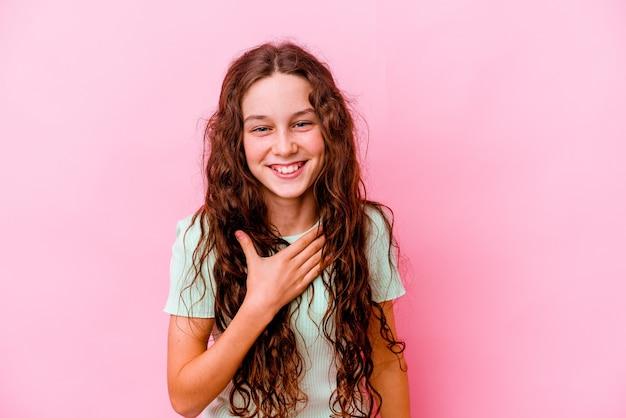 ピンクの壁に孤立した少女は胸に手を置いて大声で笑う