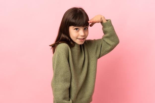 분홍색 벽에 고립 된 어린 소녀는 뭔가를 찾고 손으로 멀리 찾고