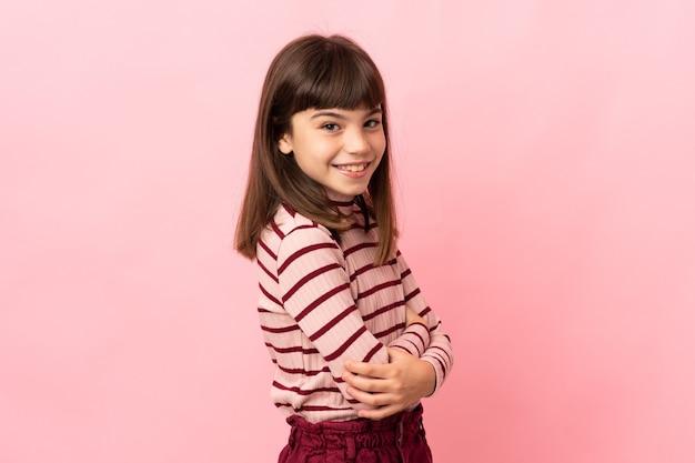 측면을보고 웃 고 분홍색 벽에 고립 된 어린 소녀