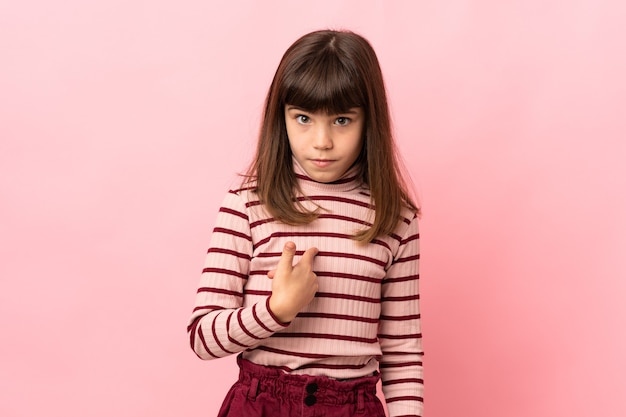 자신을 가리키는 분홍색 벽에 고립 된 어린 소녀