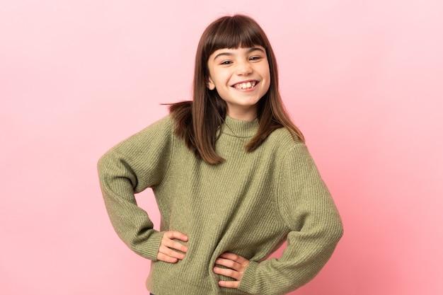 엉덩이에 팔을 포즈와 미소 핑크 벽에 고립 된 어린 소녀