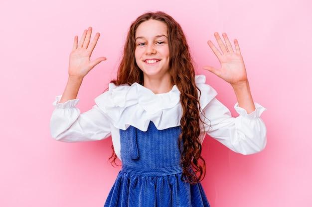 즐거운 놀라움을 받고 흥분하고 손을 올리는 분홍색 벽에 고립 된 어린 소녀
