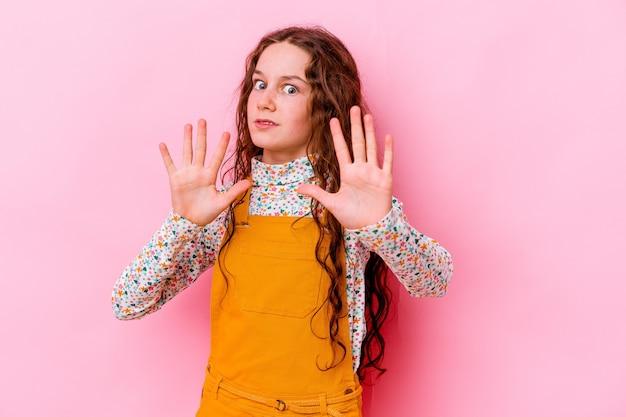 혐오의 제스처를 보여주는 누군가를 거부 분홍색 벽에 고립 된 어린 소녀