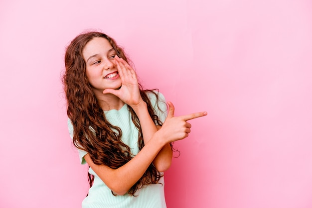 Маленькая девочка изолирована на розовой стене, говоря сплетню, указывая на сторону, сообщая что-то