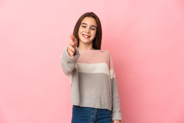 좋은 거래를 닫기 위해 악수 핑크 벽에 고립 된 어린 소녀