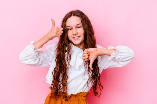 Маленькая девочка изолирована на розовой стене показывает палец вверх и палец вниз, трудно выбрать концепцию