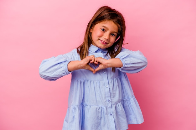 ピンクの壁に孤立した少女笑顔と手でハートの形を示しています