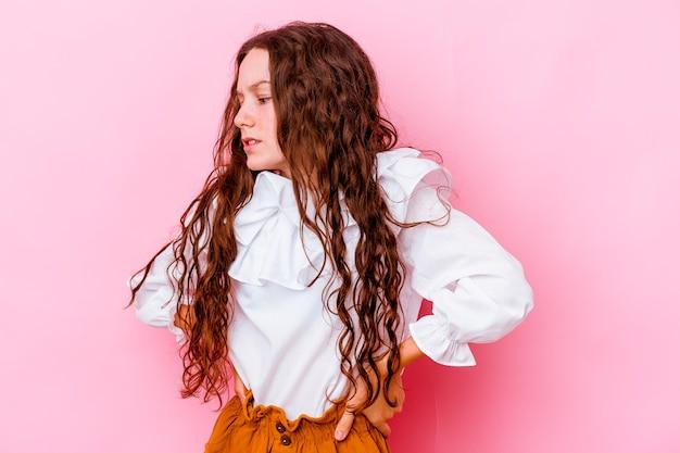 허리 통증을 겪고 분홍색 벽에 고립 된 어린 소녀