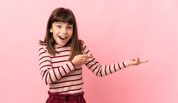 ピンクの壁に孤立した少女は驚いて側を指しています