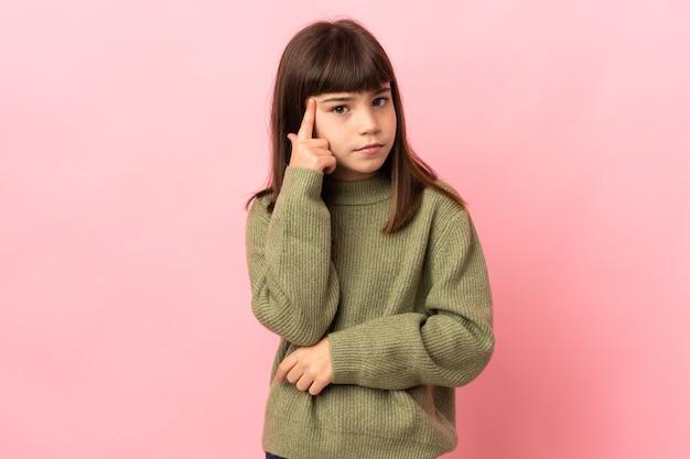 아이디어를 생각하는 분홍색 벽에 고립 된 어린 소녀