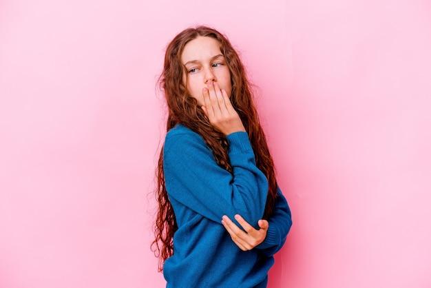 手で口を覆う疲れたジェスチャーを示すあくびをするピンクの壁に孤立した少女