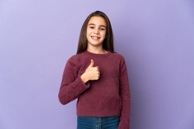 親指を立てるジェスチャーを与える紫色の背景に分離された少女