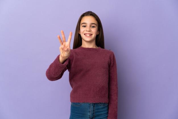 보라색 배경에 행복하고 손가락으로 세 세에 고립 된 어린 소녀