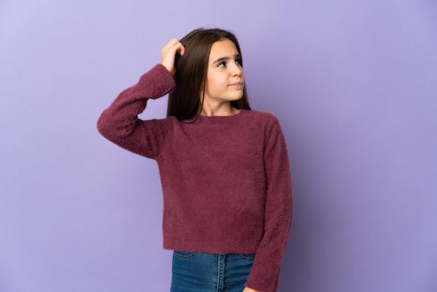 Маленькая девочка, изолированные на фиолетовом фоне, сомневаясь, почесывая голову