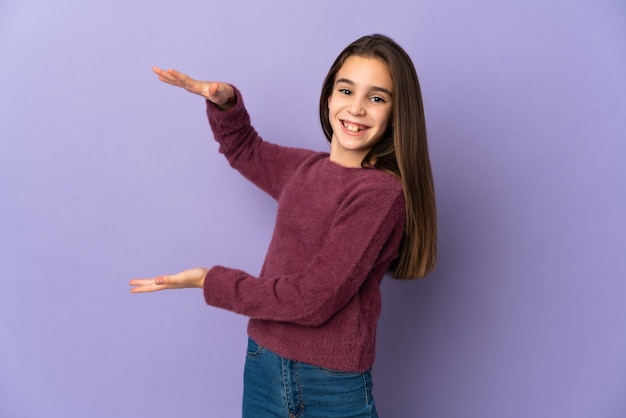 광고를 삽입하는 copyspace 들고 보라색 배경에 고립 된 어린 소녀