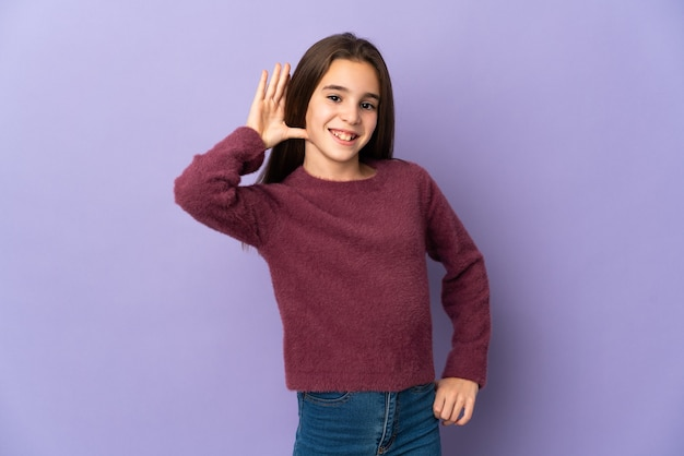 귀에 손을 넣어 뭔가를 듣고 보라색 배경에 고립 된 어린 소녀