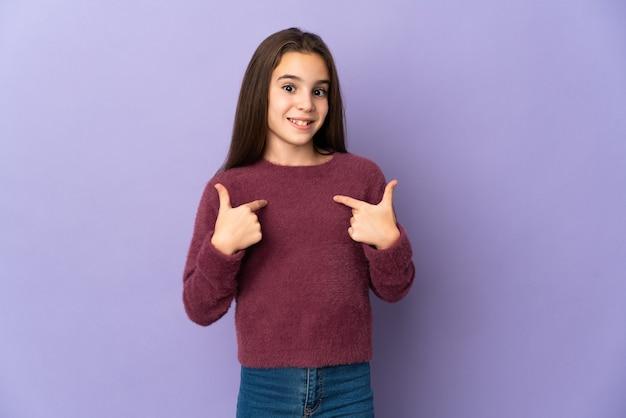 자신을 가리키는 보라색 배경에 고립 된 어린 소녀