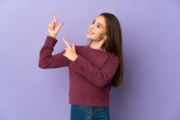 검지 손가락으로 가리키는 보라색 배경에 고립 된 어린 소녀 좋은 아이디어