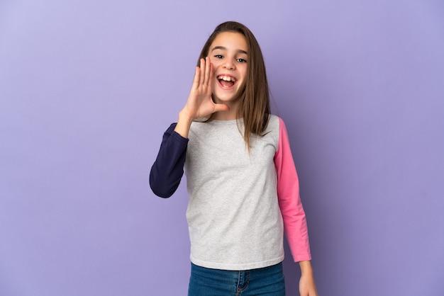 Маленькая девочка, изолированные на фиолетовом фоне, кричит с широко открытым ртом
