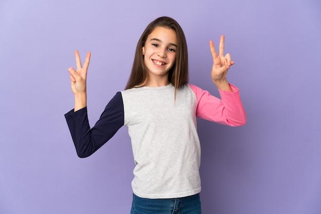 양손으로 승리 기호를 보여주는 보라색 배경에 고립 된 어린 소녀