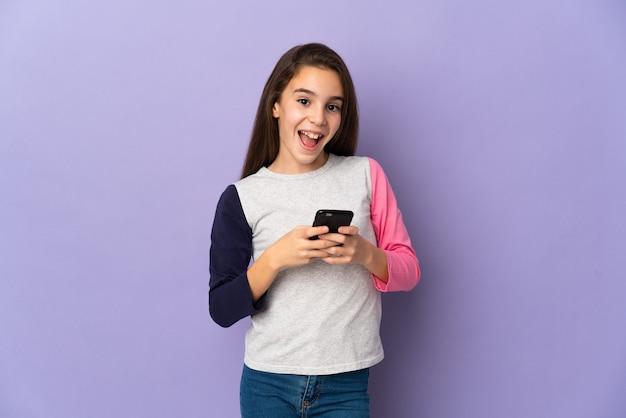 보라색 배경 놀라게 하 고 메시지를 보내는에 고립 된 어린 소녀