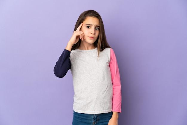 Маленькая девочка, изолированные на фиолетовом фоне, думая об идее