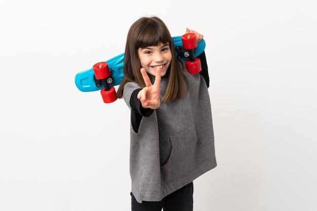 승리 제스처를 하 고 스케이트와 흰색 배경에 고립 된 어린 소녀