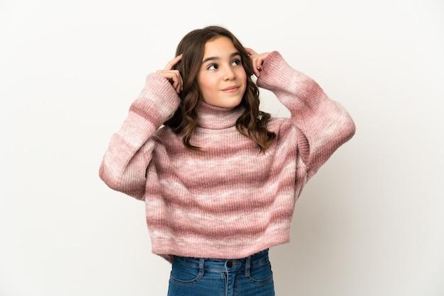 의심과 생각을 갖는 흰 벽에 고립 된 어린 소녀