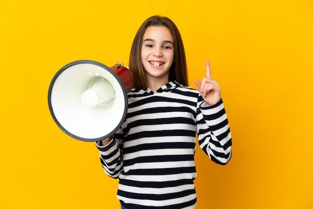 메가폰을 들고 좋은 아이디어를 가리키는 노란색 배경에 고립 된 어린 소녀