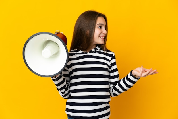 Маленькая девочка изолирована на желтом фоне с мегафоном и с удивленным выражением лица