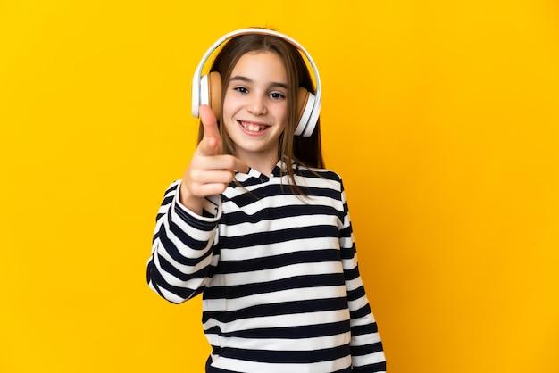 노란색 배경 음악 듣기와 앞을 가리키는에 고립 된 어린 소녀