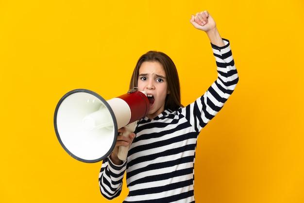 뭔가를 발표하기 위해 확성기를 통해 외치는 노란색 배경에 고립 된 어린 소녀