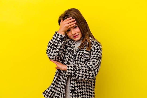 Маленькая девочка изолирована на желтой стене, моргает в камеру сквозь пальцы, смущенно закрывая лицо