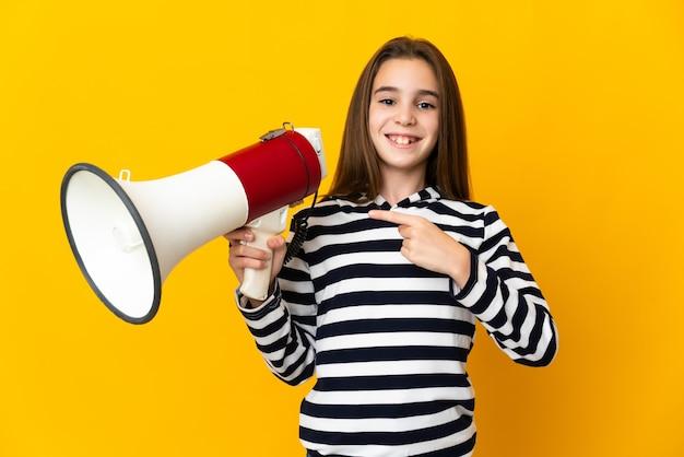 Маленькая девочка изолирована на желтой стене, держа мегафон и указывая сторону
