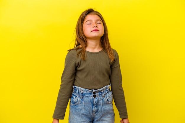 Маленькая девочка, изолированная на желтой стене, смеется и закрывает глаза, чувствует себя расслабленной и счастливой