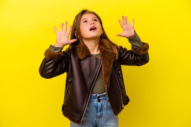 Маленькая девочка изолирована на желтой стене, крича в небо, глядя вверх, разочарованная