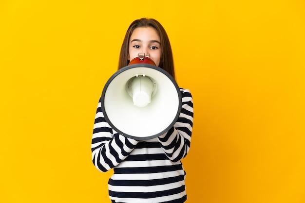 뭔가를 발표하기 위해 확성기를 통해 외치는 노란색 벽에 고립 된 어린 소녀