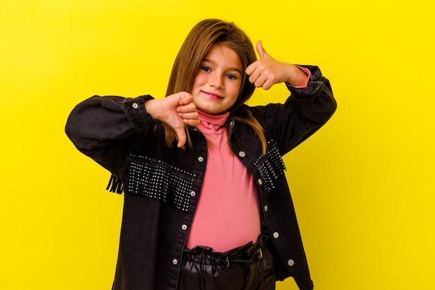 Маленькая девочка, изолированные на желтой стене, показывает палец вверх и палец вниз