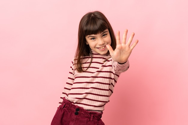 Little girl isolated on pink background counting five with fingers