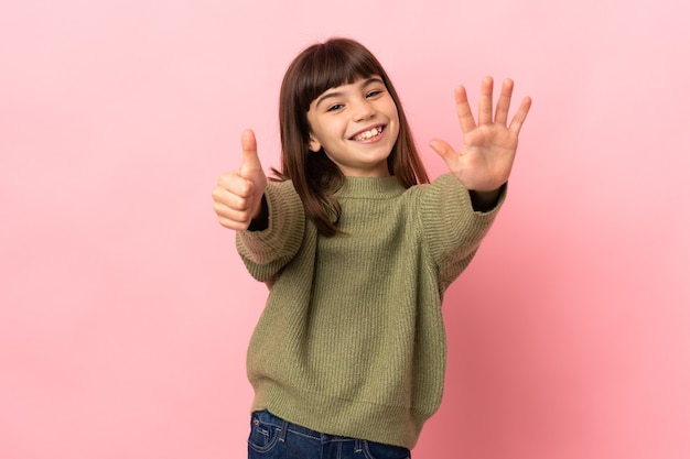 Little girl isolated on pink background counting six with fingers