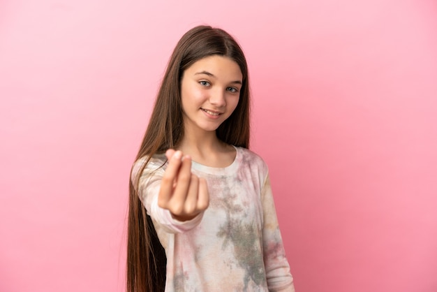 Little girl over isolated pink background making money gesture