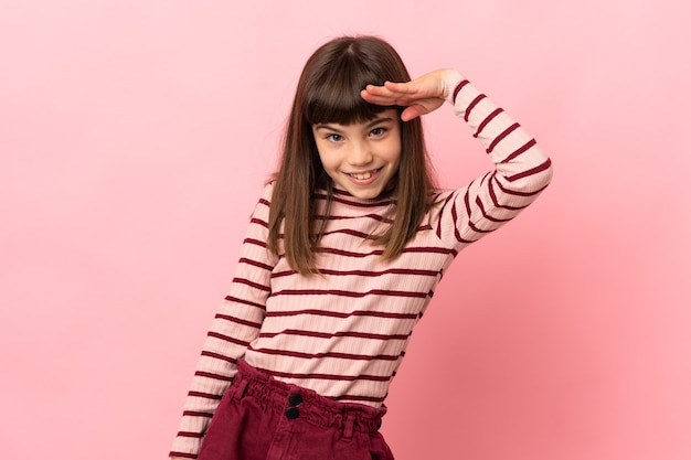 Little girl isolated on pink background saluting with hand with happy expression