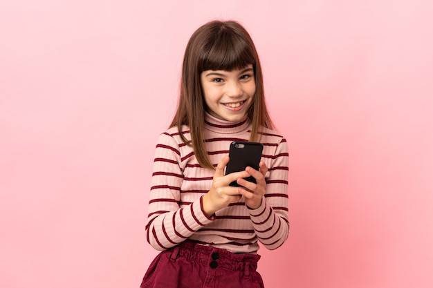 Little girl isolated on pink background sending a message with the mobile