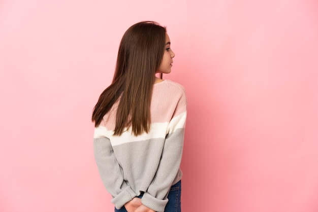 Little girl isolated on pink wall in back position and looking back