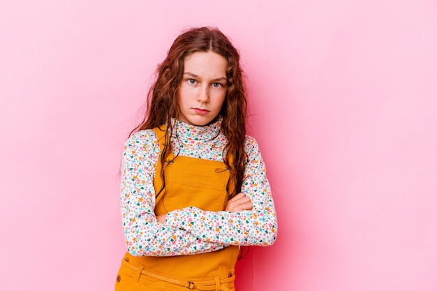 Little girl isolated on pink wall blows cheeks, has tired expression. facial expression concept