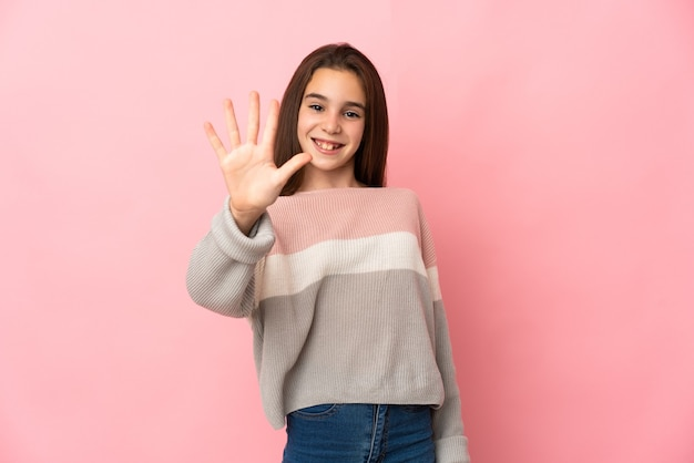 Little girl isolated on pink wall counting five with fingers