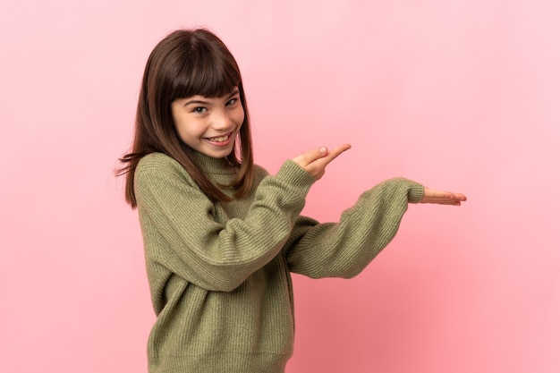 Little girl isolated on pink wall holding copyspace imaginary on the palm to insert an ad