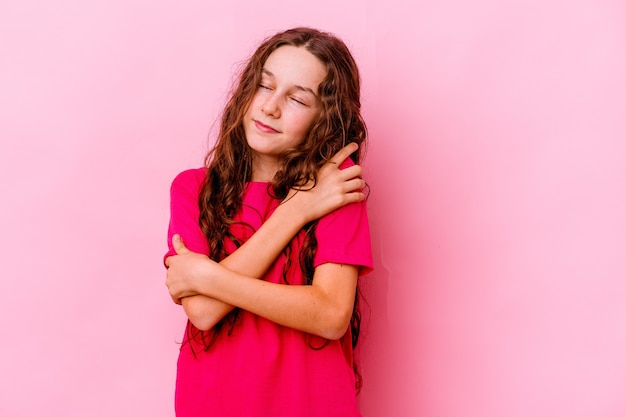 Little girl isolated on pink wall hugs, smiling carefree and happy