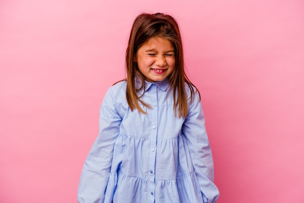 Little girl isolated on pink wall  laughs and closes eyes, feels relaxed and happy